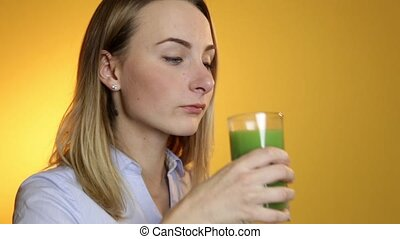 Young woman drinking green vegetable smoothie