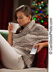 Young woman drinking hot chocolate and watching TV in front of Christmas tree