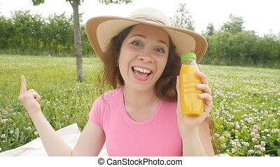 Young woman drinking juice in a park