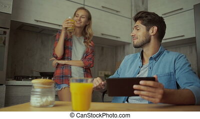 Young woman drinking jus, man using tablet at home.