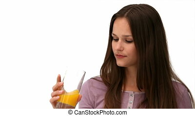 Young woman drinking orange juice against a white background
