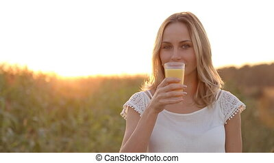 Young woman drinking orange juice outside