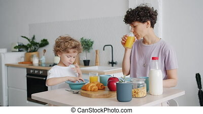 Young woman drinking orange juice while son eating cereal at...