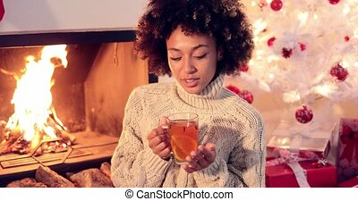 Young woman drinking spicy lemon tea in front of the...