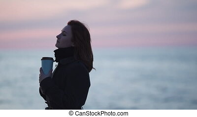 Young woman drinking take away coffee outdoors on a beach during a cold blue sunset with clear reflection in water on the Baltic Sea