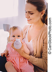 Young woman drinking tea while her baby drinking water