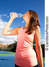 young woman drinking water after a game of tennis.