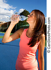 young woman drinking water after a tennis game.