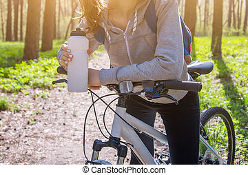 Young woman drinking water after riding a bicycle