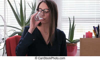 Young woman drinking water at the work