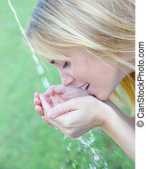 Young woman drinking water from fountain