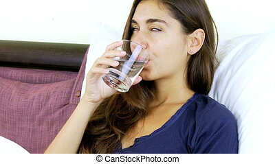 Young woman drinking water in bed