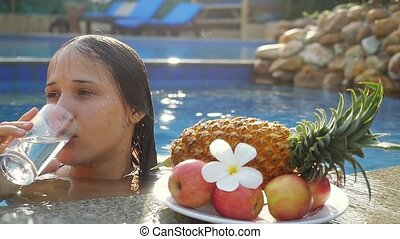 Young woman drinking water while sunbathing in the pool at...