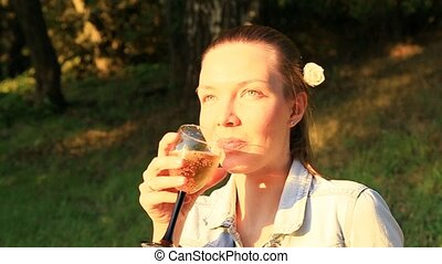 young woman drinking wine outside