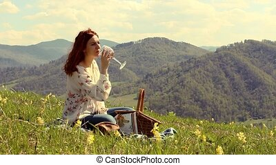 woman drinking wine sitting on a green meadow high in the mountains