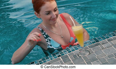 young woman drinks a cocktail in the pool
