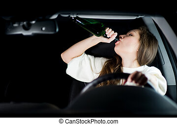 young woman drinks alcohol while driving and not looking at the road