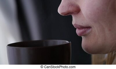 Young woman drinks coffee or tea near the window. slow motion