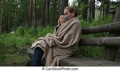 Young woman drinks hot coffee or tea near mountain river....
