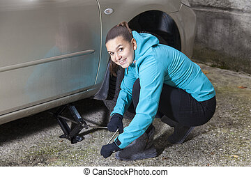 Young woman driver changes car tyre