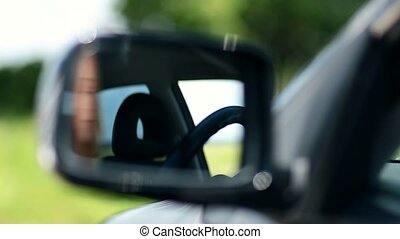 Young woman driver looking at car side view mirror
