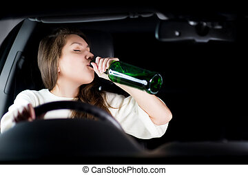 young woman drives a car at night and drinks alcohol while driving. copy space