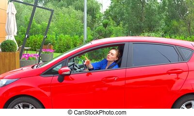 Young woman drives red car with small pushes on parking lot....
