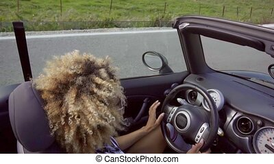 Young woman driving a cabriolet - Young woman with a trendy...