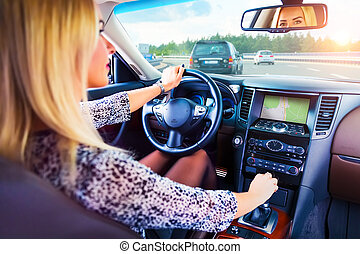 Young woman driving a car on a highway