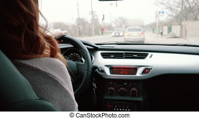 young woman driving a car, rear view