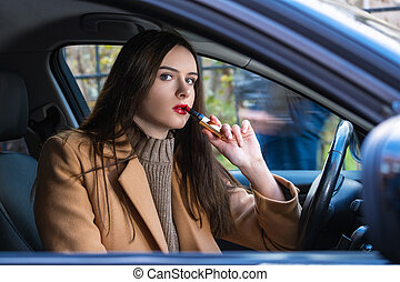 young woman driving a car with lipstick in her hands
