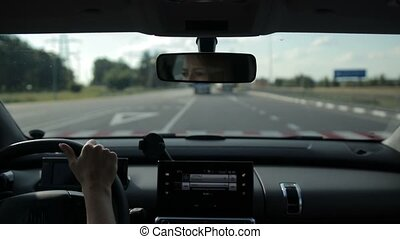 Young woman driving car on highway in sunlight