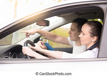 Young woman driving, man pointing the direction