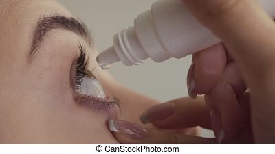 Young woman drops eyes with eyedropper. Close-up view.
