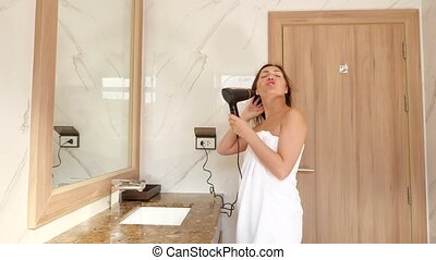 young woman drying hair at in bathroom