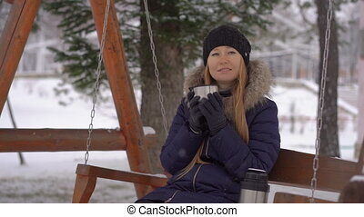 Young woman during snowfall sits on a bench and drinks hot ...