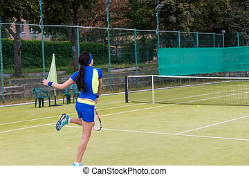 Young woman during the game on a tennis court