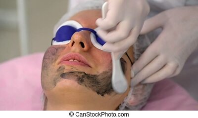 Young woman during the procedure in the cosmetology clinic -...
