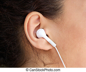 Young woman ear with earphone - Close up young woman ear...