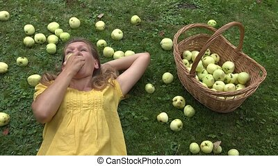 young woman eat fresh apple lying on grass in summer garden.