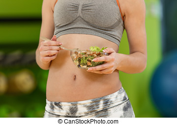 Young woman eating a healthy vegetables salad after workout. Fitness and healthy lifestyle concept.