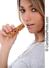 young woman eating a nut bar