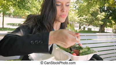 Young woman eating a nutritious healthy mixed green salad with strawberries