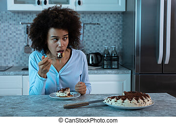 Young Woman Eating A Piece Of Cake At Night