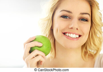 Young woman eating an apple at home