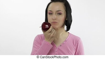 Young woman eating apple and says yum. Girl takes first bite...