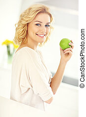Young woman eating apple in the kitchen