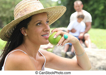 young woman eating apple in the park