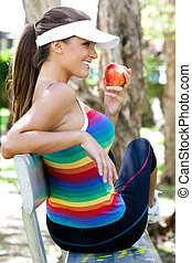 Young Woman Eating Apple on Park Bench