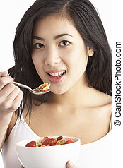 Young Woman Eating Bowl Of Healthy Breakfast Cereal In Studio